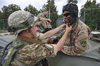 Ein Ukrainer zeigt einem Amerikaner, wie man eine Panzerhaube à la russe anlegt / Bild: EPA/MYKOLA TYS