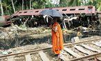 Ein buddhistischer Mönch bei einem der entgleisten Waggons der