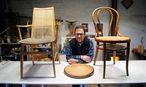 Der Sesselflechter Robert Roth vor seinem aktuellen Werkstück, einem Thonetstuhl aus den 1960er-Jahren. / Bild: Die Presse