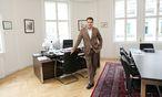 Aslan Kurtaran in seinem Büro im ersten Bezirk. Hier empfängt er Expats aus der ganzen Welt, um ihnen den Anfang in Wien zu erleichtern. / Bild: (c) Stanislav Jenis