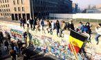 Berliner sitzen auf der Mauer nach der Wiedervereinigung in Berlin / Bild: imago