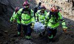 Hilfsteams bergen eine Leiche. / Bild: REUTERS