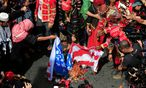 Demonstranten in traditioneller Kleidung verbrennen US-Fahnen vor der amerikanischen Botschaft in Manila.  / Bild: REUTERS