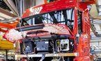 Mitarbeiter bei der Montage von Fahrgestell Motor und Getriebe mit dem Fahrerhaus bei der MAN Truc / Bild: (c) imago/imagebroker (imago stock&people)