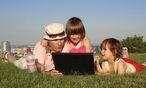 Frau und Kinder mit Notebook auf einer Wiese / Bild: www.BilderBox.com