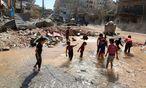 Abkühlung zwischen den Luftangriffen. Kinder stapfen durch eine gewaltige Lacke, die sich nach dem Treffer einer Wasserleitung ergossen hat. Schmutziges Wasser in Aleppos Straßen führt zu Krankheiten.  / Bild: REUTERS