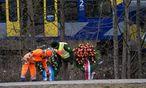 Ein Feuerwehrmann und ein Polizist mit Kränzen am Ort des Zugunglücks nahe Bad Aibling in Bayern. / Bild: (c) APA/dpa/Sven Hoppe (Sven Hoppe)