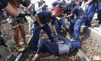 Flüchtlinge wehren sich, vom Zug in ein Auffanglager gebracht zu werden. / Bild: REUTERS