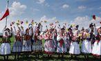 Warten auf Franziskus. Traditionell gekleidete Polinnen harrten der Ankunft von Papst Franziskus auf dem Krakauer Flughafen Johannes Paul II.  / Bild: (c) APA/AFP/JOE KLAMAR