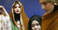 Models wear creations from the MSF collection backstage at the Islamic Fashion Festival in Kuala Lumpur