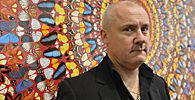 British artist Damien Hirst poses next to his painting ´I Am Become Death, Shatterer of Worlds´, at the Tate Modern gallery in London