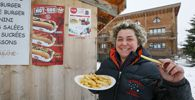 Valerie Maertens, manager of La Cabane, a chip stall, poses with a plate of French fries in Val d´Isere, French Alps