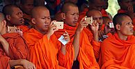 Buddhists monks use mobile phones to take pictures of a performance based on the Khmer Rouge regime during the annual ´Day of Anger´ ceremony at the Choeung Ek ´Killing Fields´ site, located on the outskirts of Phnom Penh
