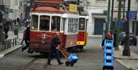 Men push crates of bottles of water near a tram in downtown Lisbon