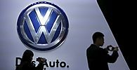 Guests stand next to a Volkswagen logo at the stage of the company at the 16th Shanghai International Automobile Industry Exhibition in Shanghai