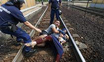Hungarian policemen stand by the family of migrants as they wanted to run away at the railway station in the town of Bicske / Bild: (c) REUTERS (LASZLO BALOGH)