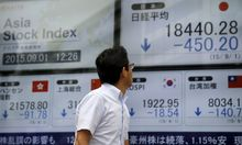 Man looks at electronic boards displaying various Asian countries´ stock price indexes outside a brokerage in Tokyo