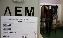 A woman leaves a booth on her way to cast a ballot at a polling station in Limassol