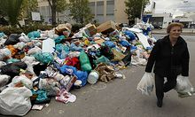 An elderly woman carries shopping bags as she passes next to a pile of rotting garbage in the port of