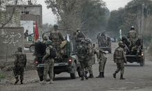 Soldiers arrive and take position near the site of a police station after it was attacked in Bannu
