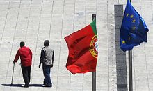 Two men walk under the flags of Portugal and the European Union, right,  Thursday, July 21, 2011, in