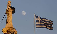 The moon rises behind the 19th century statue of the ancient goddess Athena as a Greek flag billows a