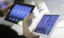 A couple compares an Apple third generation iPad to an iPad 2 on display at an Apple reseller store i