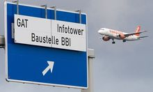 A planes approaching Schoenefeld SFX airport flies near a sign denoting the motorway exit to the building site of the Berlin Brandenburg international airport in Schoenefeld
