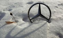 German car manufacturer Daimler's characteristic Mercedes-Benz star is seen on a snow covered vehicle in Bucharest