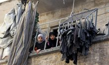 Women look out from a damaged balcony after an air strike on the rebel held al-Saliheen district in Aleppo