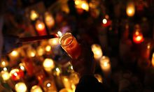 A candle is lit at a memorial for Sandy Hook Elementary School shooting victims in Newtown