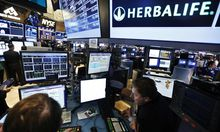 Traders work at the post that trades Herbalife stock on the floor of the New York Stock Exchange