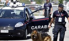 Italian paramilitary police officer searches for explosives with a dog at the accreditation center in