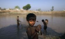In this Monday, Nov. 1, 2010 picture, Shwun Ali, a boy whose family was displaced by floods, looks on
