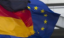 A European, right, and a German flag fly in the wind at the Place of the Republic in Berlin, Thursday