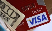 FILE - This file photo taken Tuesday, May 3, 2011 shows a Visa card in a wallet in Richardson, Texas.
