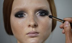 Model waits as her make-up is applied before a show during Fashion Week in Singapore