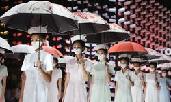 Models wearing masks hold umbrellas as they perform during the TORAY Liu Wei Collection segment at China Fashion Week in Beijing