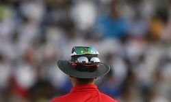Umpire Palliyaguruge places his sunglasses on his hat during the second One Day International cricket match between Sri Lanka and South Africa in Pallekele