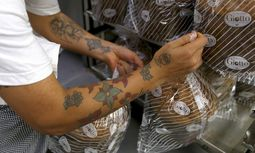 Prison baker places some panettone cakes on rack at the Pasticceria Giotto in Padua´s Due Palazzi prison / Bild: (c) REUTERS (� Alessandro Bianchi / Reuters)