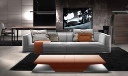 Schnittig. Sofa, Lounge Chair, Sideboard. In das typische Aston-Martin- Grau mischt sich schon einmal ein Klecks sattes Orange. / Bild: (c) Beigestellt