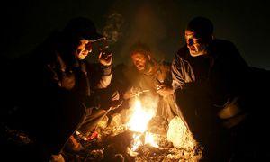 Irans Suchtkranke zwischen Methadon und harten Drogen. Betroffene Männer scharen sich um ein Feuer in einem Vorort von Teheran. / Bild: Ebrahim Noroozi / AP / picturedesk.com