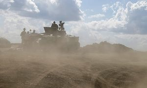 Ukrainian army servicemen around an armoured vehicle are seen through dust raised by passing vehicles near Debaltseve / Bild: (c) REUTERS (GLEB GARANICH)