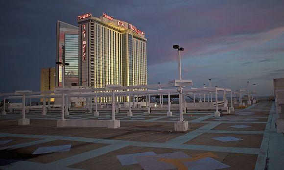 The illuminated Trump Taj Mahal Casino is seen from an empty rooftop parking lot at dusk in Atlantic City, New Jersey