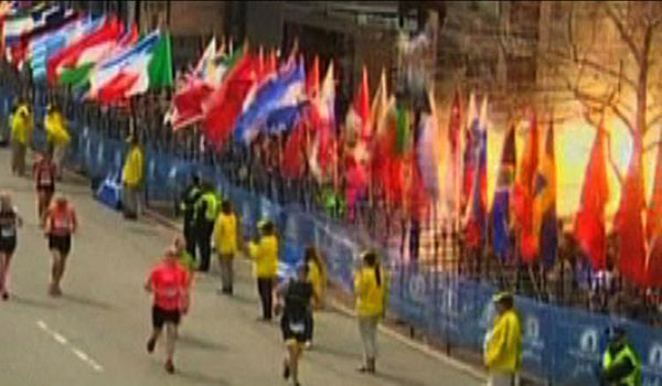 A runner is escorted from the scene after explosions went off at the 117th Boston Marathon in Boston / Bild: (c) REUTERS (HANDOUT)