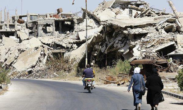 Zivilisten am Montag in einem zerstörten Stadtteil von Homs / Bild: APA/AFP/LOUAI BESHARA
