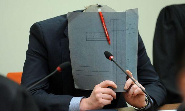 Holger G. verbirgt sein Gesicht hinter einer Mappe. Er gibt an, seit 2004 aus der rechten Szene ausgestiegen zu sein. / Bild: (c) EPA