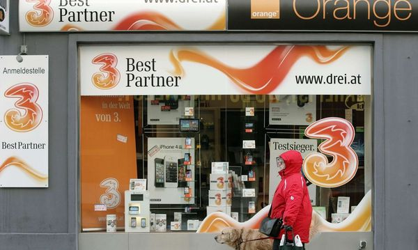 A woman and her dog walk by a telecommunications store advertising 'Orange' and '3' in Vienna / Bild: REUTERS