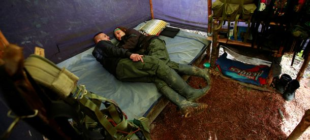A couple from the 51st Front of the Revolutionary Armed Forces of Colombia (FARC) rest inside a tent at a camp in Cordillera Oriental